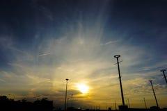 Puesta del sol y nubes en el cielo con los posts de la lámpara de la silueta Fotografía de archivo