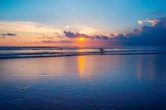 Puesta del sol y personas que practica surf del océano Fotos de archivo libres de regalías