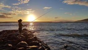Puesta del sol y pescador fotos de archivo