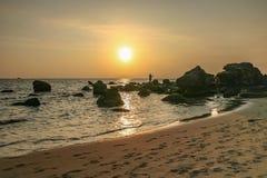 Puesta del sol y piedra volcánica en la isla de Phu Qhoc Foto de archivo