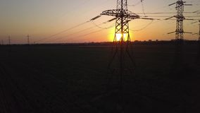 Puesta del sol y pilón de alto voltaje del poder metrajes