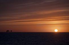 Puesta del sol y plataforma petrolera Foto de archivo