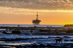 Puesta del sol y plataforma petrolera Imagenes de archivo