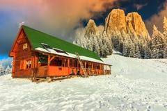 Puesta del sol y refugio coloridos, Cárpatos, Transilvania, Rumania, Europa del invierno Foto de archivo libre de regalías