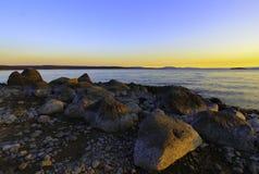 Puesta del sol y rocas del lago Imágenes de archivo libres de regalías