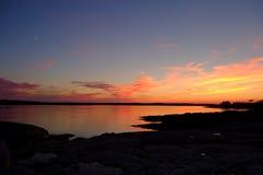 Puesta del sol y salida de la luna sobre la bahía Foto de archivo libre de regalías