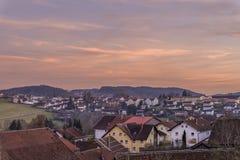 Puesta del sol y tarde-rojo en el bosque bávaro con la vista de la ciudad Grafenau Fotografía de archivo libre de regalías