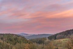 Puesta del sol y tarde-rojo en el bosque bávaro con la vista de la montaña Lusen Fotos de archivo