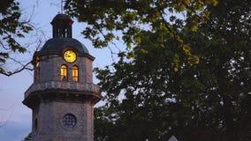 Puesta del sol y torre de reloj vieja en el centro de ciudad de Varna, Bulgaria Se?al popular de la ciudad almacen de video
