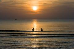 Puestas del sol en el mar con la gente de la silueta en el agua y las nubes y la onda en el océano y el barco Foto de archivo libre de regalías