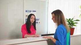 Puesto de informaciones de la recepción Cliente de ayuda auxiliar femenino de la mujer almacen de metraje de vídeo
