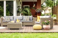 Pufe e flores amarelos ao lado da mobília do jardim do rattan no woode imagens de stock