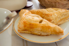 Puff. A pair of chicken puff setup on a white small plate on a dining table Royalty Free Stock Photos