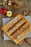 Puff apple pie. Homemade desserts. A composition with a pie, apples and herbs. Background of burlap Stock Images
