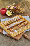 Puff apple pie. Homemade desserts. A composition with a pie, apples and herbs. Background of burlap Stock Photos