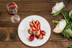 Puff cake with cream, chocolate and strawberry, on a wooden table. Top view. Close-up Stock Photos