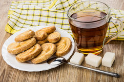 Puff cookies in plate, hot tea, teaspoon and lumpy sugar Stock Image