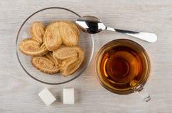 Puff cookies in saucer, transparent cup with tea, lumpy sugar Stock Photos