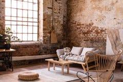 Puff och trätabell på matta nära fönster i wabisabiinre med soffan och fåtöljen royaltyfri bild