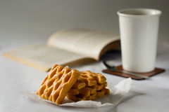 Puff pastries on the background  cup and book. Cookies piece of parchment open book and Cup Royalty Free Stock Photography