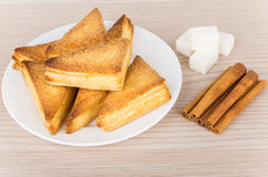 Puff pastries in plate, pieces of  lumpy sugar and cinnamon Stock Images