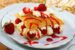 Puff pastries  with strawberries and berry sauce. Royalty Free Stock Image