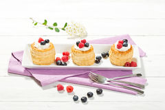 Puff pastries with vanilla-icecream and cream, blueberries and r Stock Photography