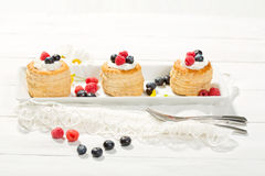 Puff pastries with vanilla-icecream and cream, blueberries and r Royalty Free Stock Photography
