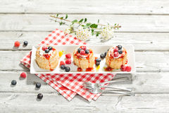 Puff pastries with vanilla-icecream and cream, blueberries and r Stock Photo