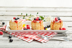 Puff pastries with vanilla-icecream and cream, blueberries and r Royalty Free Stock Photo