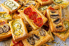 Puff pastry appetizers with vegetables, mushrooms, tomatoes, zucchini and cheese. Puff pastry appetizers with vegetables, mushrooms, tomatoes, zucchini and stock image