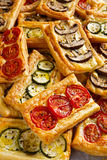 Puff pastry appetizers with vegetables, mushrooms, tomatoes, zucchini and cheese. Puff pastry appetizers with vegetables, mushrooms, tomatoes, zucchini and stock photo