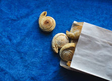 Puff pastry bagel roll. View from above of fresh baked homemade sweet puff pastry bagel roll as spiral with sugar and cinnamon in paper bag on blue jeans cloth Royalty Free Stock Photo
