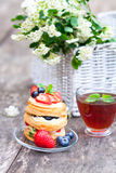 Puff pastry with berries and beautiful bouquet of white flowers Royalty Free Stock Photo