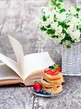 Puff pastry with berries old book and beautiful bouquet of white Stock Photography