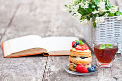 Puff pastry with berries old book and beautiful bouquet of white Royalty Free Stock Photo