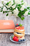Puff pastry with berries old book and beautiful bouquet of white Royalty Free Stock Photography
