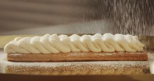 Puff pastry cake with cream and sugar falling on it stock footage