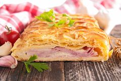 Puff pastry with cheese and bacon. On wood Stock Images