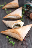 Puff pastry cheese and spinach triangles. On wooden table Royalty Free Stock Image