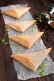 Puff pastry cheese and spinach triangles. On wooden table Stock Photos