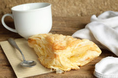 Puff pastry. With coffee cup on wooden table Royalty Free Stock Photo