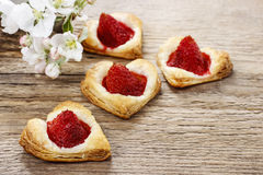 Puff pastry cookies in heart shape filled with strawberries Royalty Free Stock Image