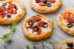 Puff pastry mini pizza. With herbs, olives and sausages Stock Photography