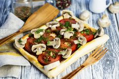 Puff pastry pie with tomatoes and mushrooms. On a wooden board stock photos