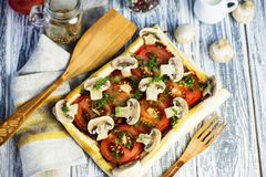 Puff pastry pie with tomatoes and mushrooms. On a wooden board stock photo