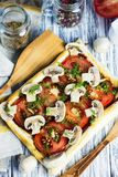 Puff pastry pie with tomatoes and mushrooms. On a wooden board royalty free stock image