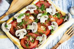 Puff pastry pie with tomatoes and mushrooms. On a wooden board royalty free stock images