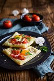 Puff pastry pies with egg, bacon, mushrooms and tomato. Savory puff pastry pies with egg, bacon, mushrooms and tomato stock photography