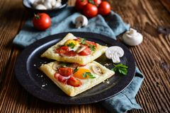 Puff pastry pies with egg, bacon, mushrooms and tomato. Savory puff pastry pies with egg, bacon, mushrooms and tomato stock photo